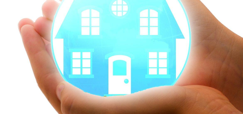 Dłonie trzymające niebieskie logo domu