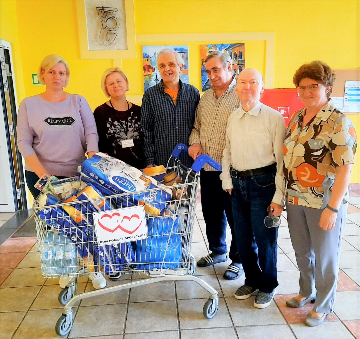 Grupa uśmiechniętych osób stojących na holu, koło nich wózek z zakupami