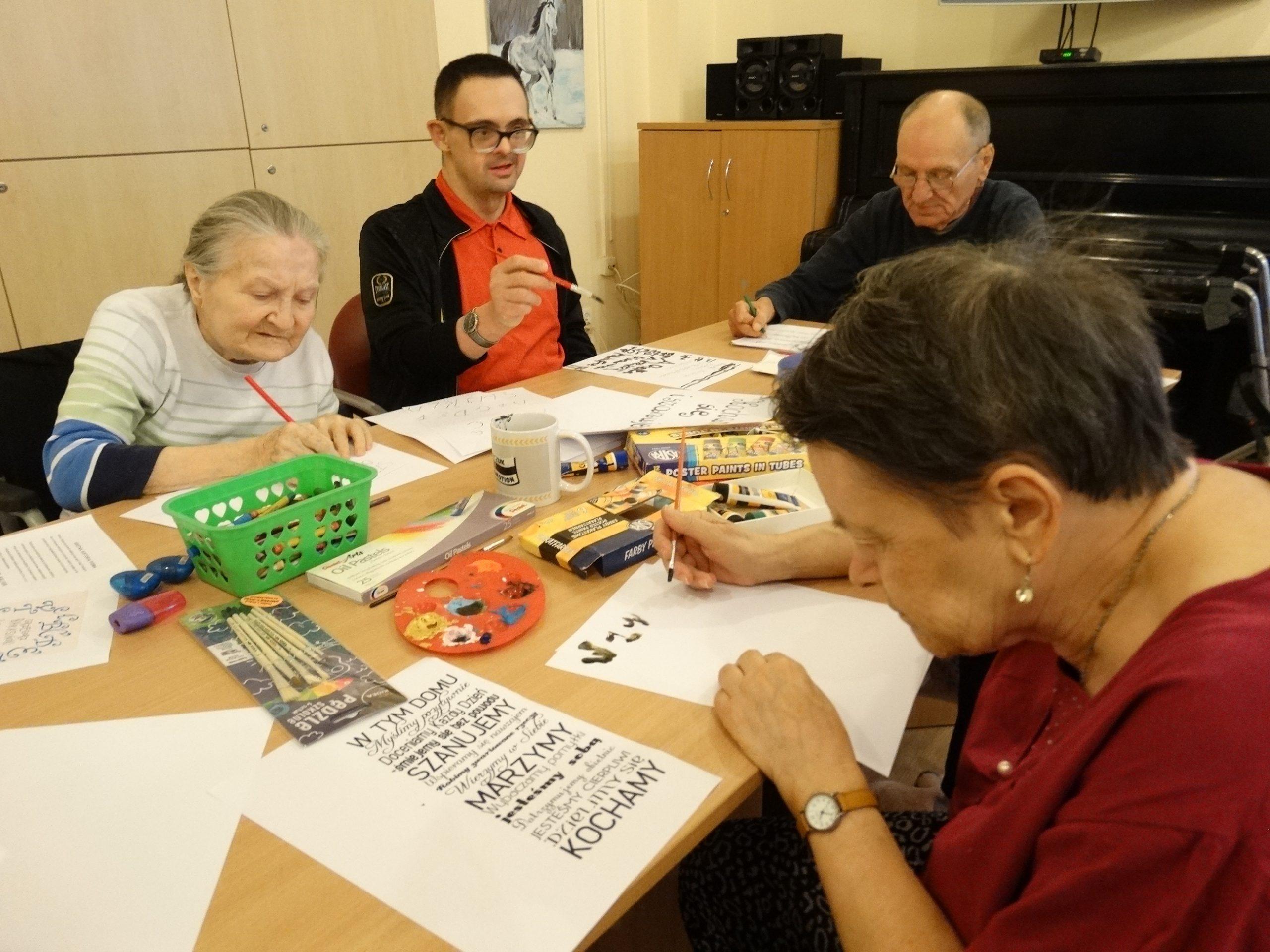 Grupa Mieszkańców zapisuje tekst na kartkach w trakcie warsztatów poligarficznych