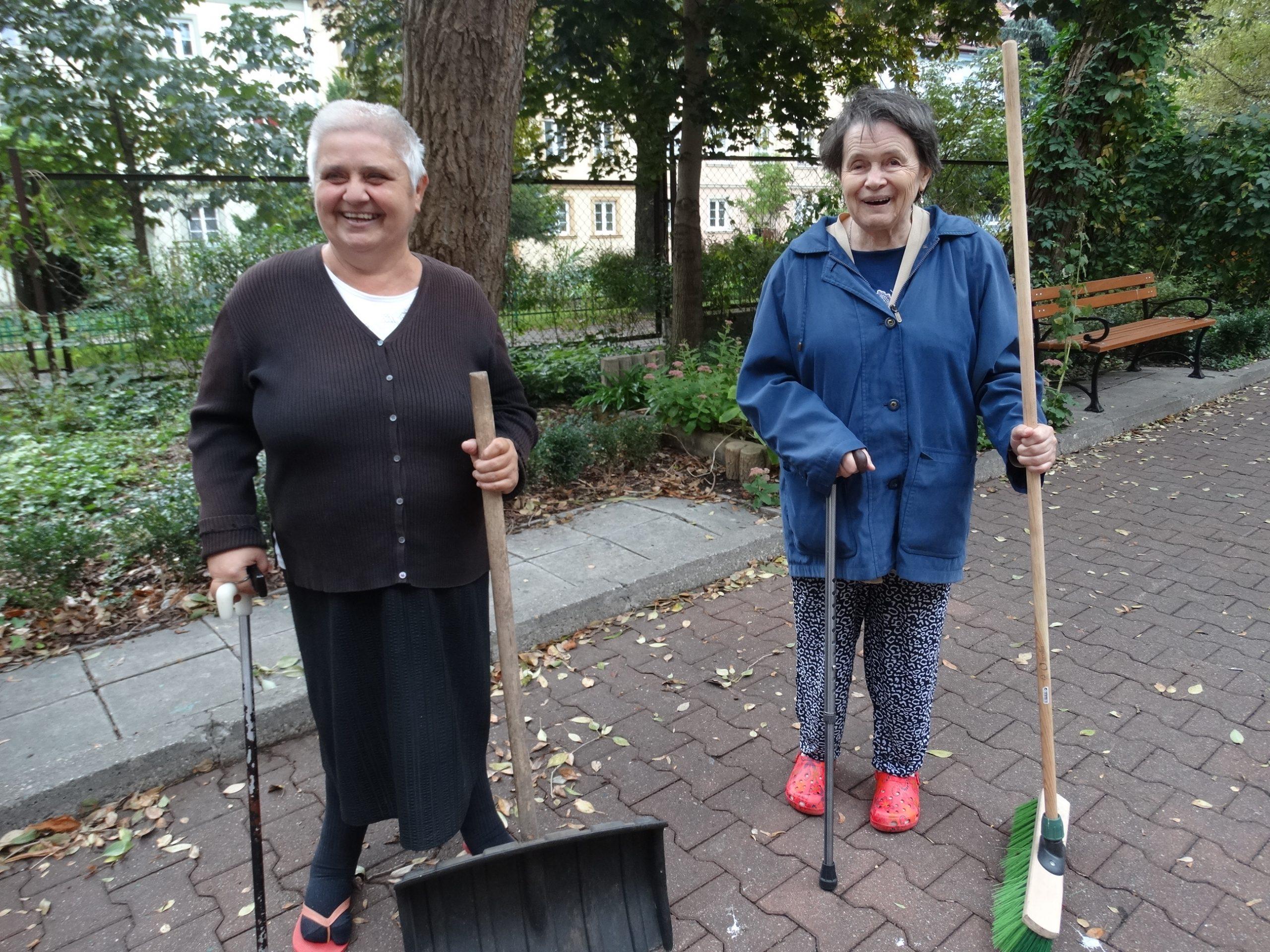 Dwie uśmiechnięte seniorki w trakcie jesiennych porządków na patio