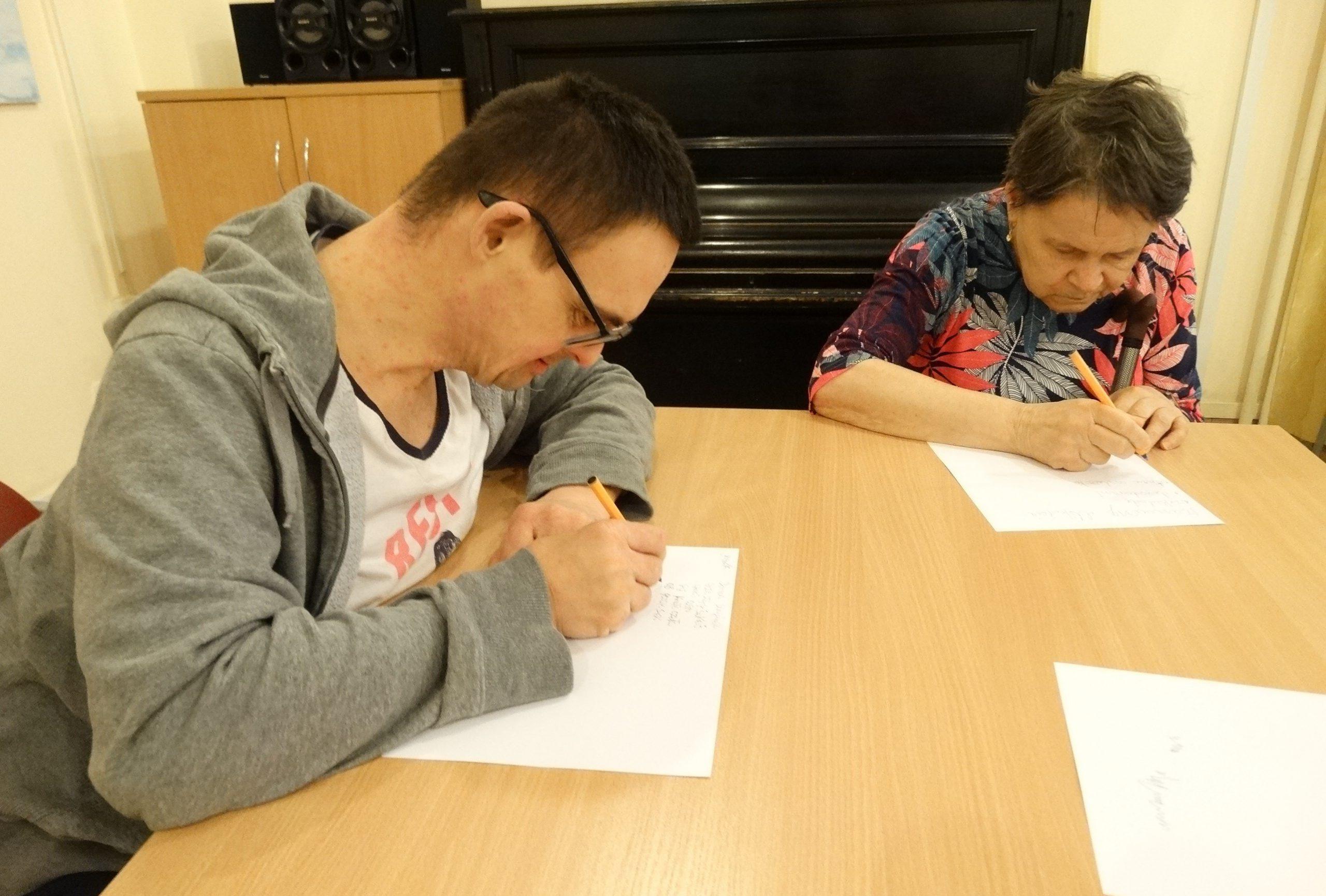 Mężczyzna i kobieta siedzą przy stole, zapisują coś na kartkach