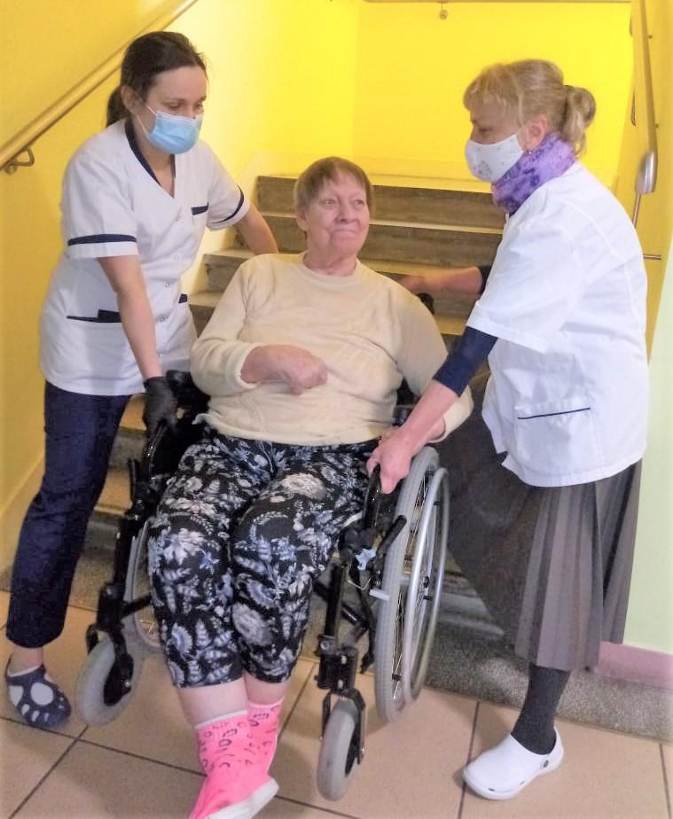 Dwie pracownice wnoszące po schodach kobiete na wózku