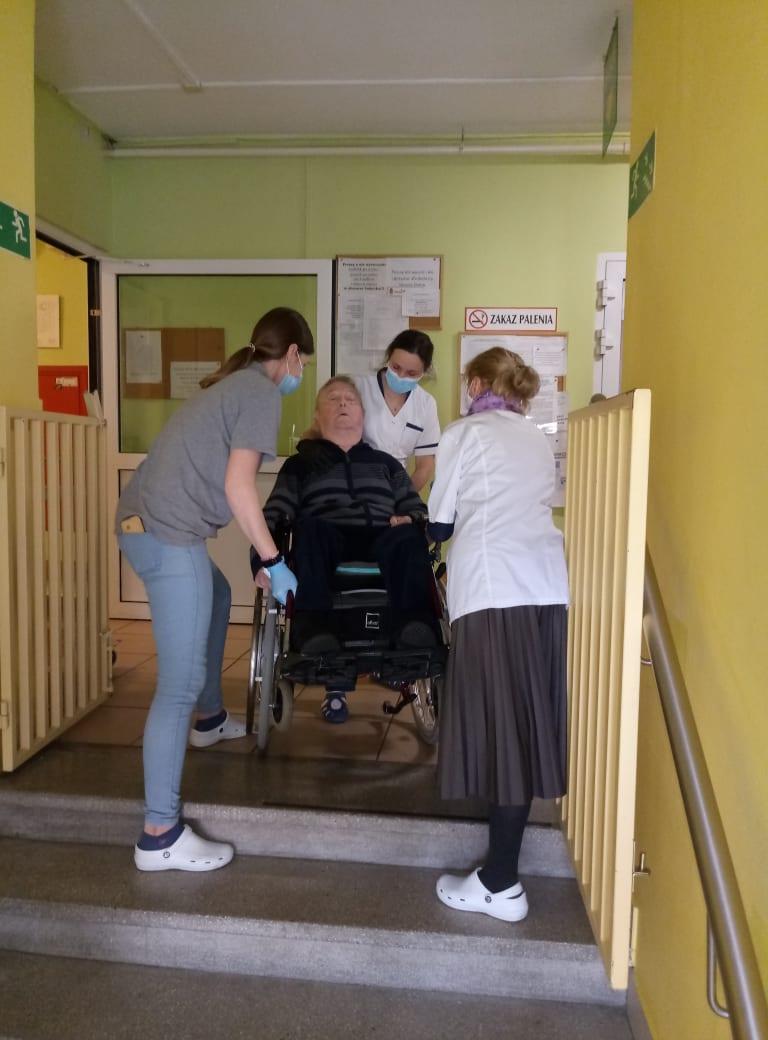 Trzy pracownice wnoszące po schodach meżczyzne na wózku