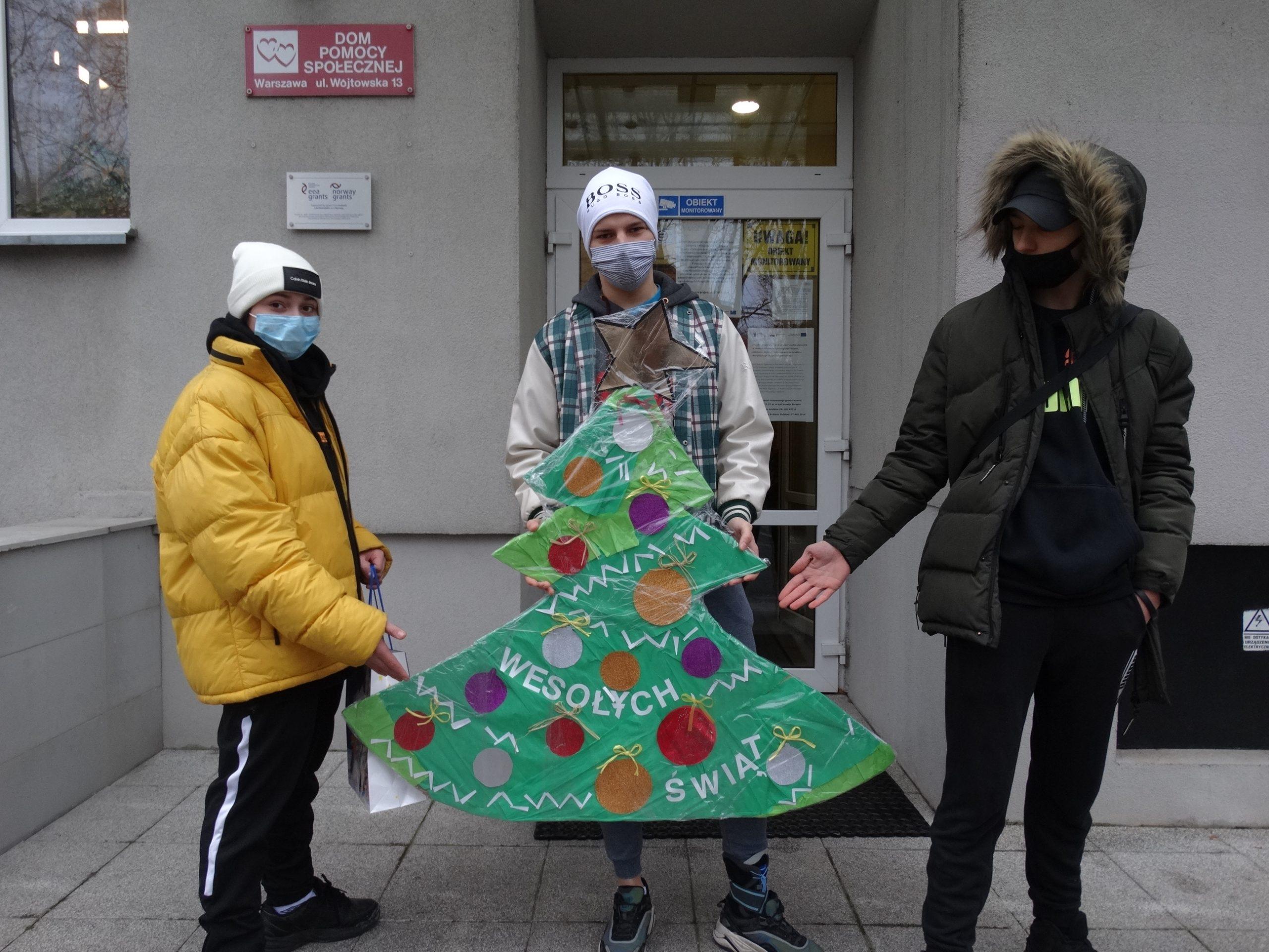 Trzech wychowanków SOW stojących przed wejściem do DPS , pozujących z własnoręcznie wykonaną choinką z tektury