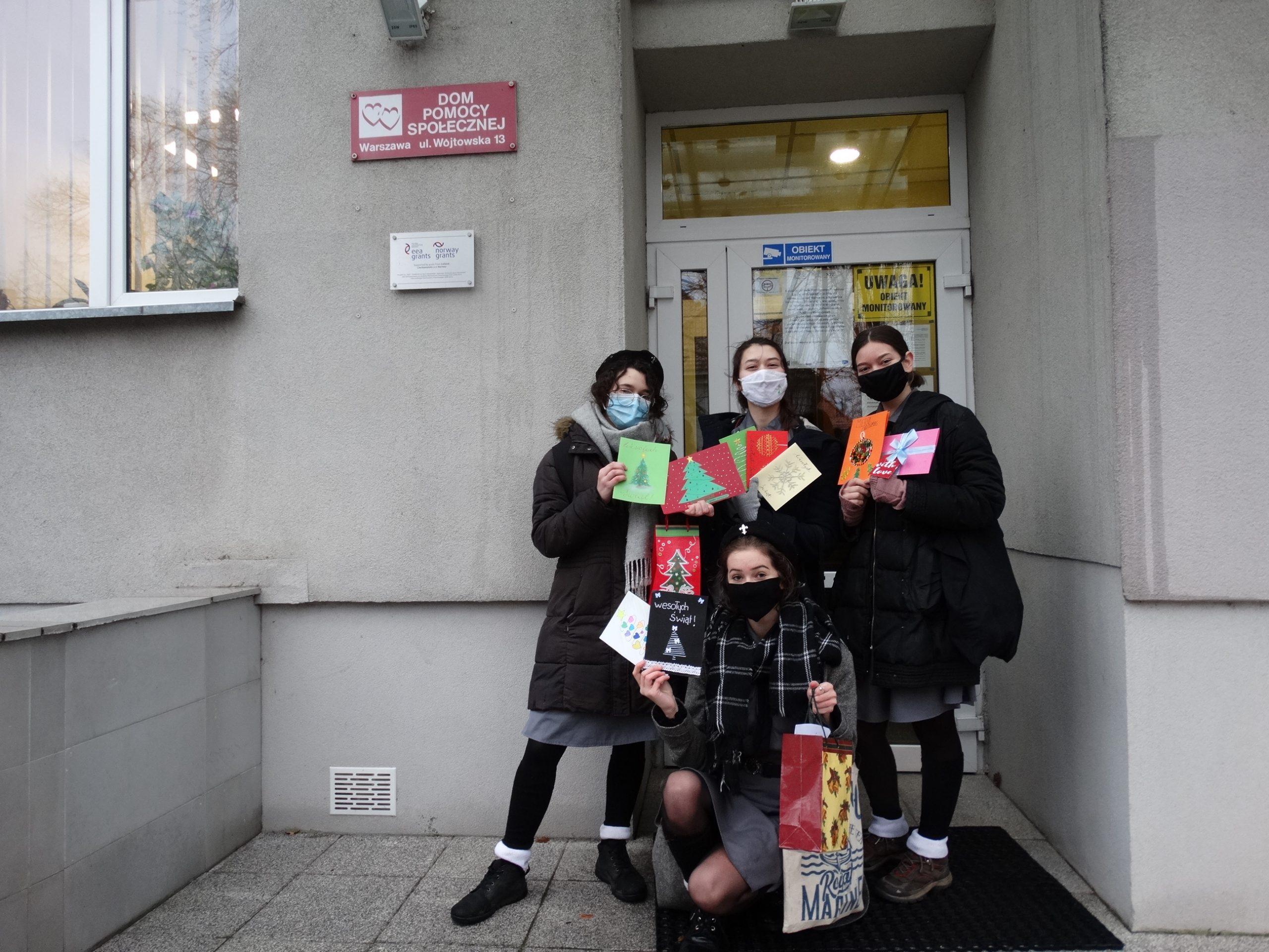 Cztery Harcerki przed wejściem do Domu pozują z kartami świątecznymi