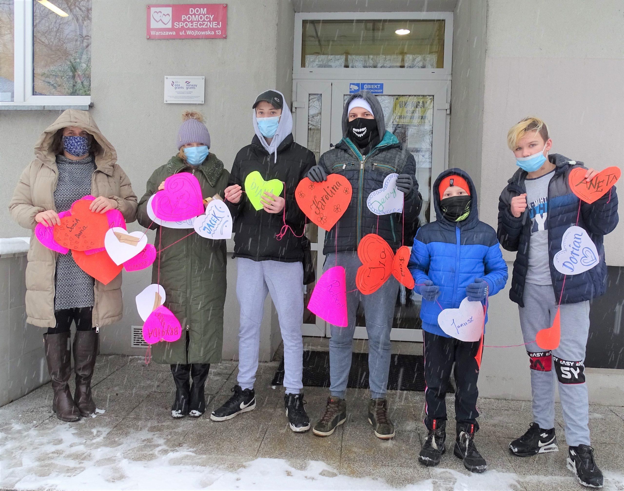 Młodzież stojąca przed wejściem do budynku z kolorowymi sercami
