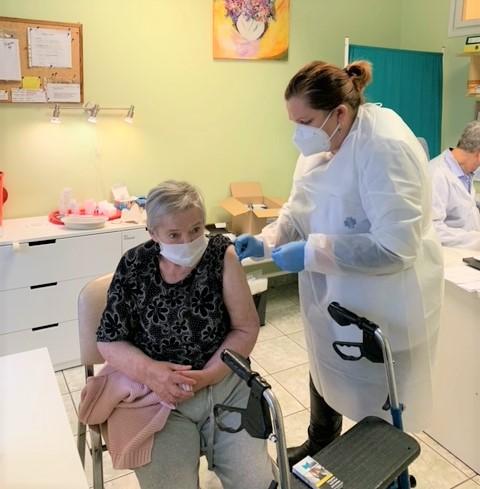 Pielęgniarka szczepi starszą kobietę