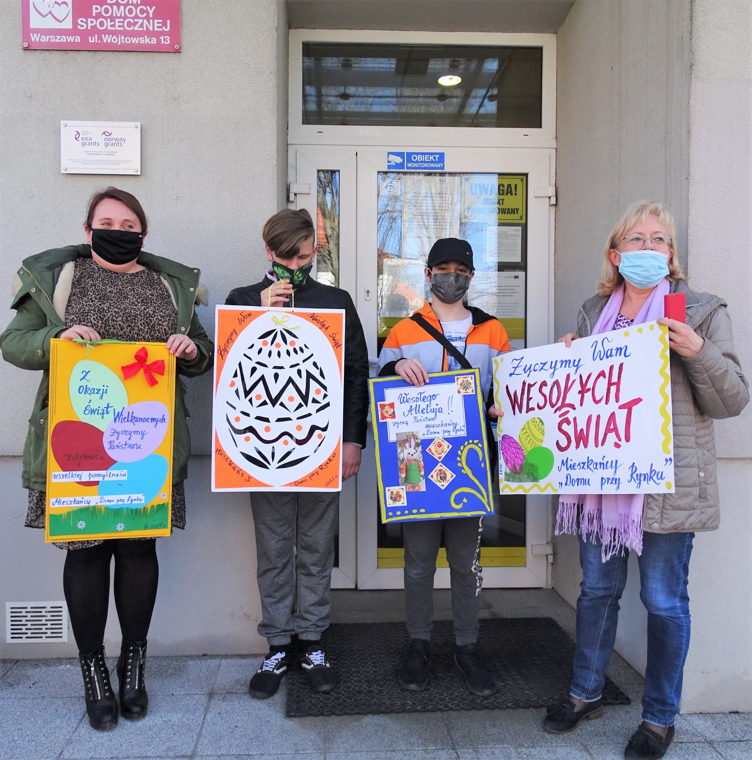 Dwie kobiety i dwoch wychowanków SOW pozujących przed wejściem do budynku trzymających plakaty wielkanocne