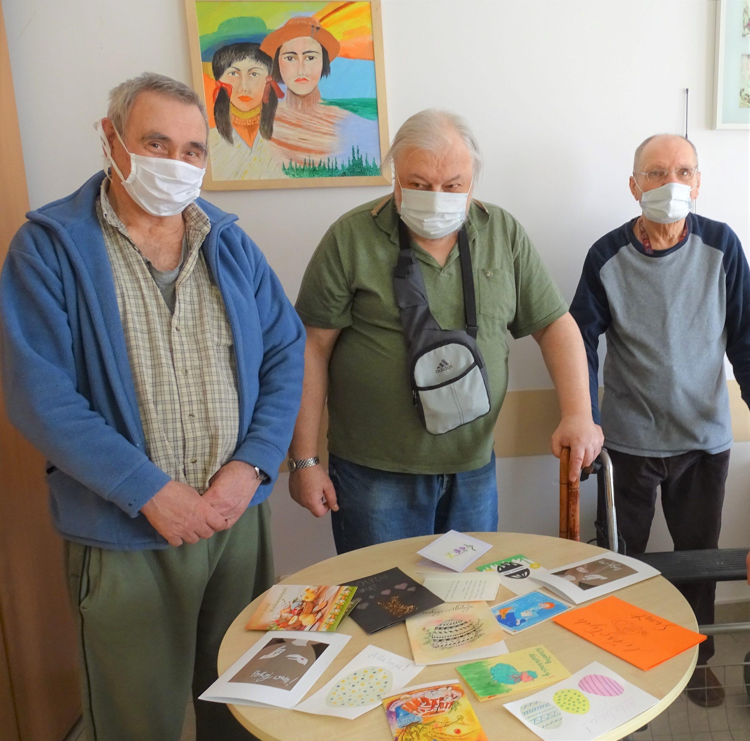 Trzech seniorów w tle leżące na stole karty świąteczne