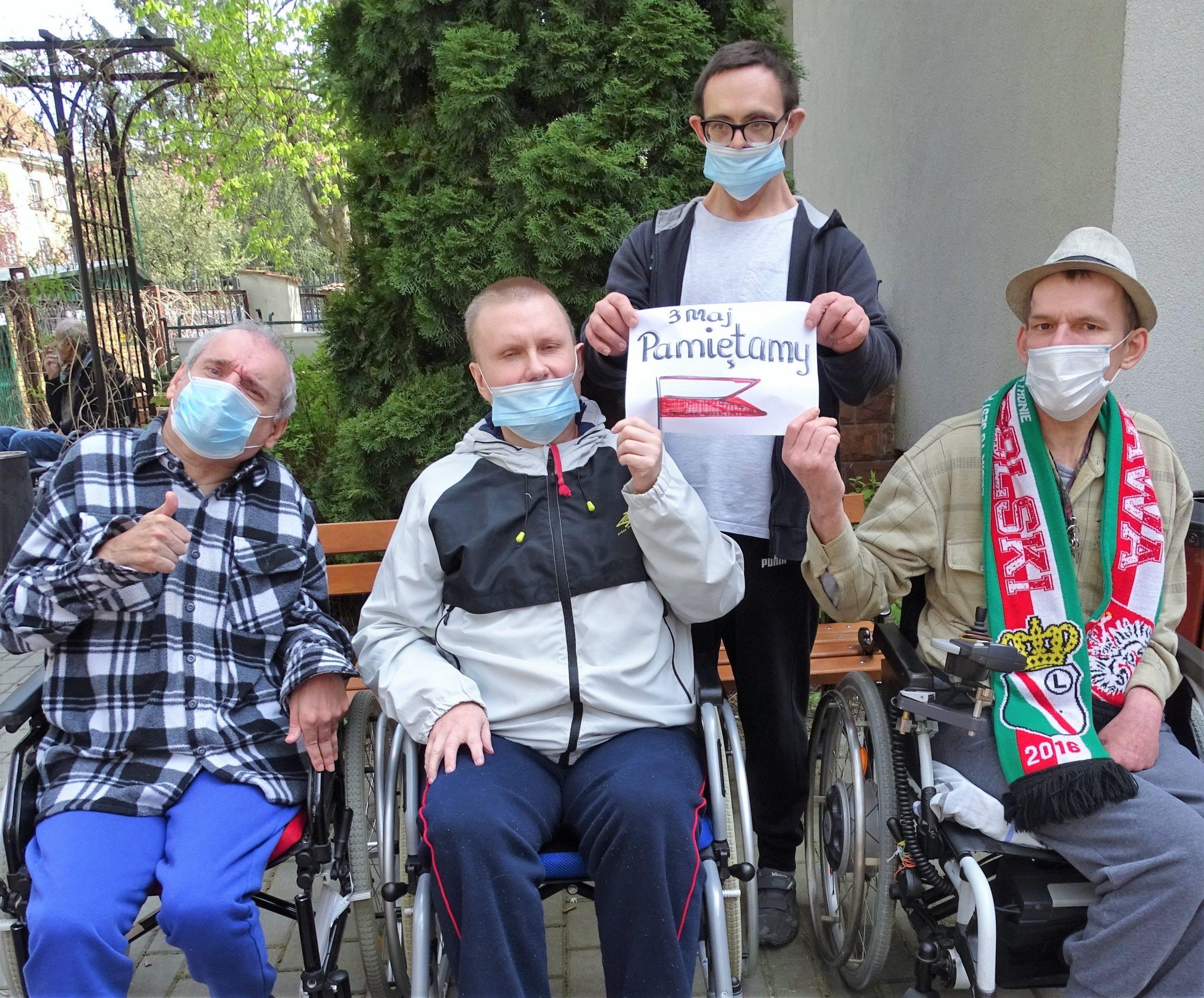 czterech mężczyzn z plakatem polskiej flagi