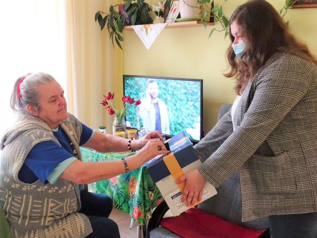 Starsza kobieta wrzuca kartę wyborczą do urny