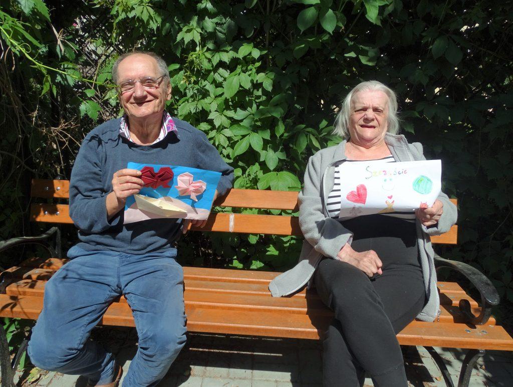 uśmiechnięci seniorzy siedzą na ławce i pokazują karty z pozdrowieniami od młodzieży