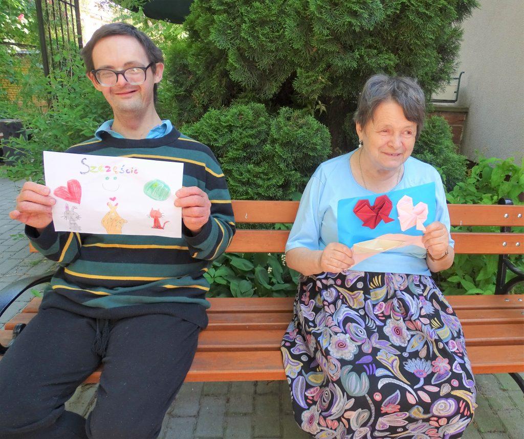Dwoje uśmiechniętych Mieszkańców Domu siedzi na ławce i pokazuje karty z pozdrowieniami od młodzieży