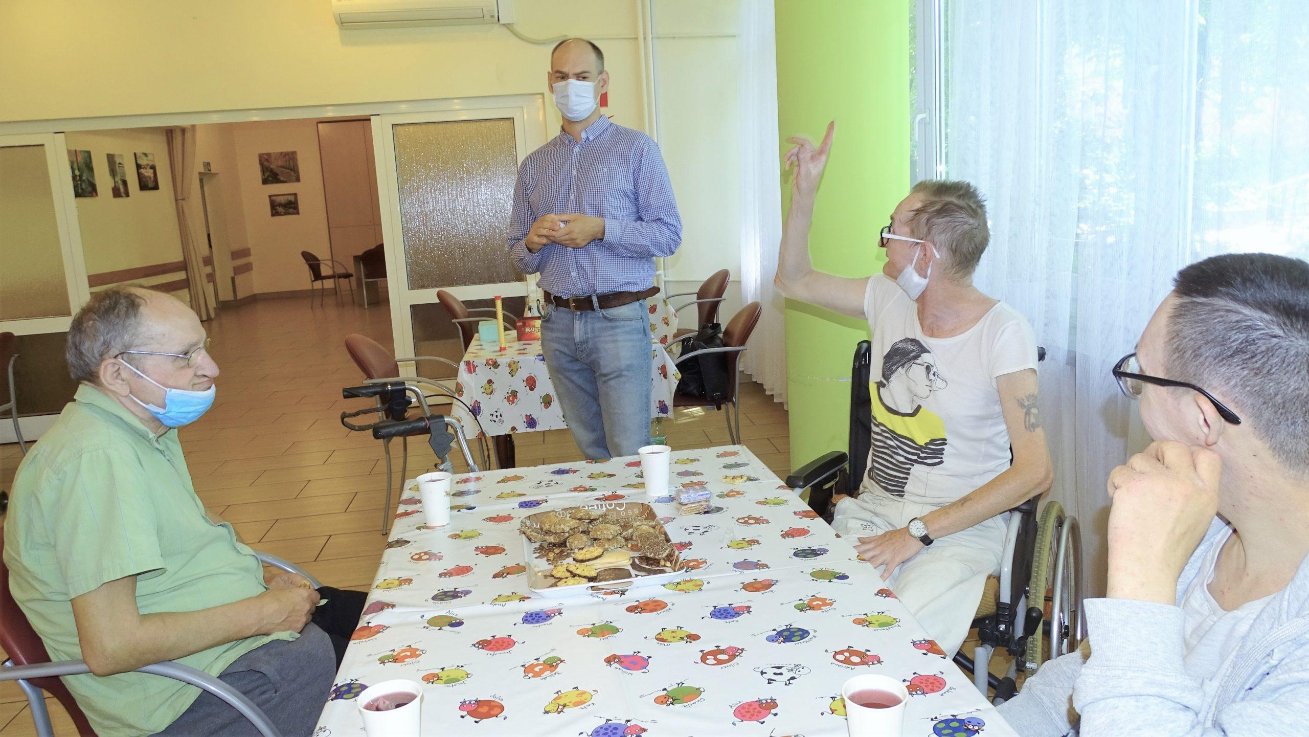 trzech mężczyzn siedzi przy stole, jeden z nich unosi rękę do góry. Obok mężczyzn stoi prowadzący warsztaty