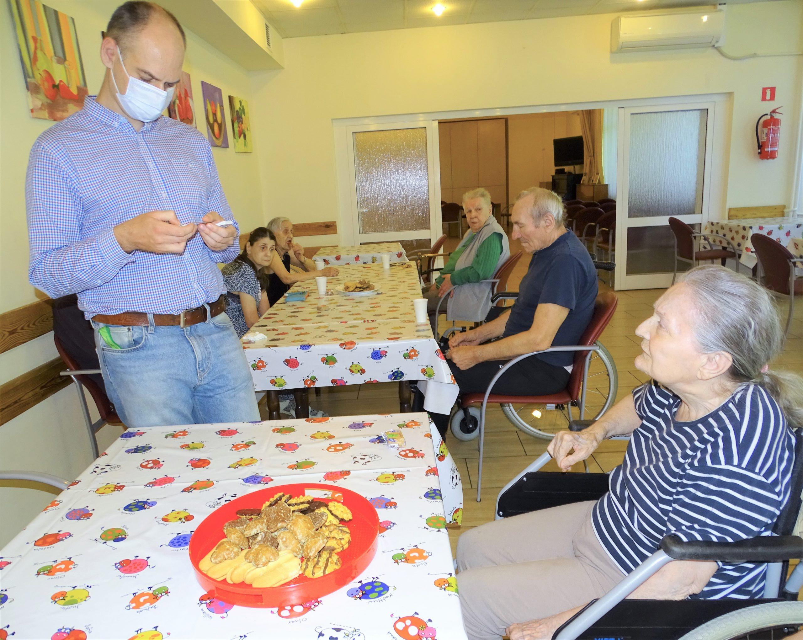 starsza kobieta siedzi przy stole na którym leży taca z ciastkami, koło niej stoi prowadzący warsztaty