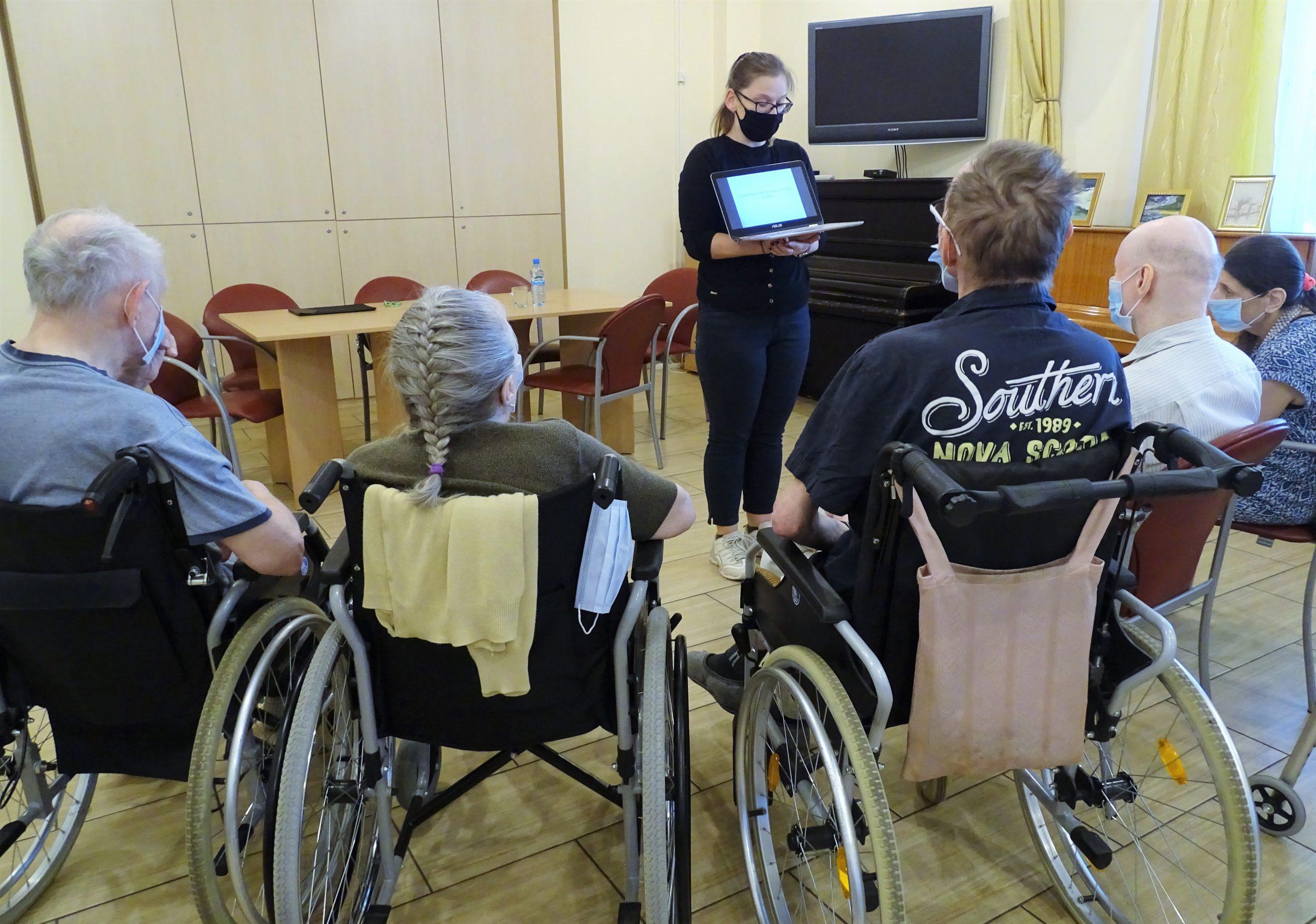 Prowadząca wykład stoi z laptopem i pokazuje ekran Mieszkańcom