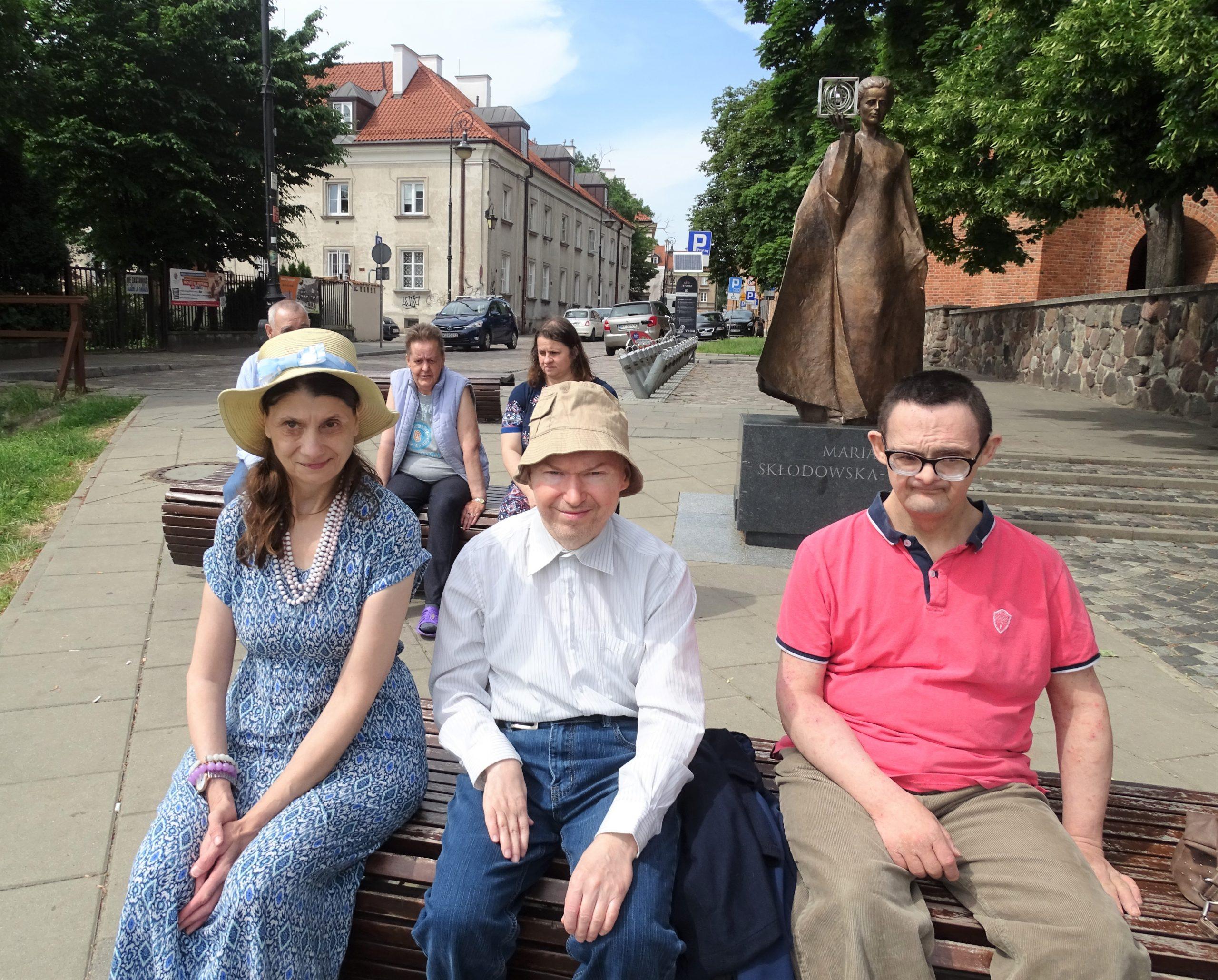 grupa Mieszkańców siedzi na ławkach na starówce