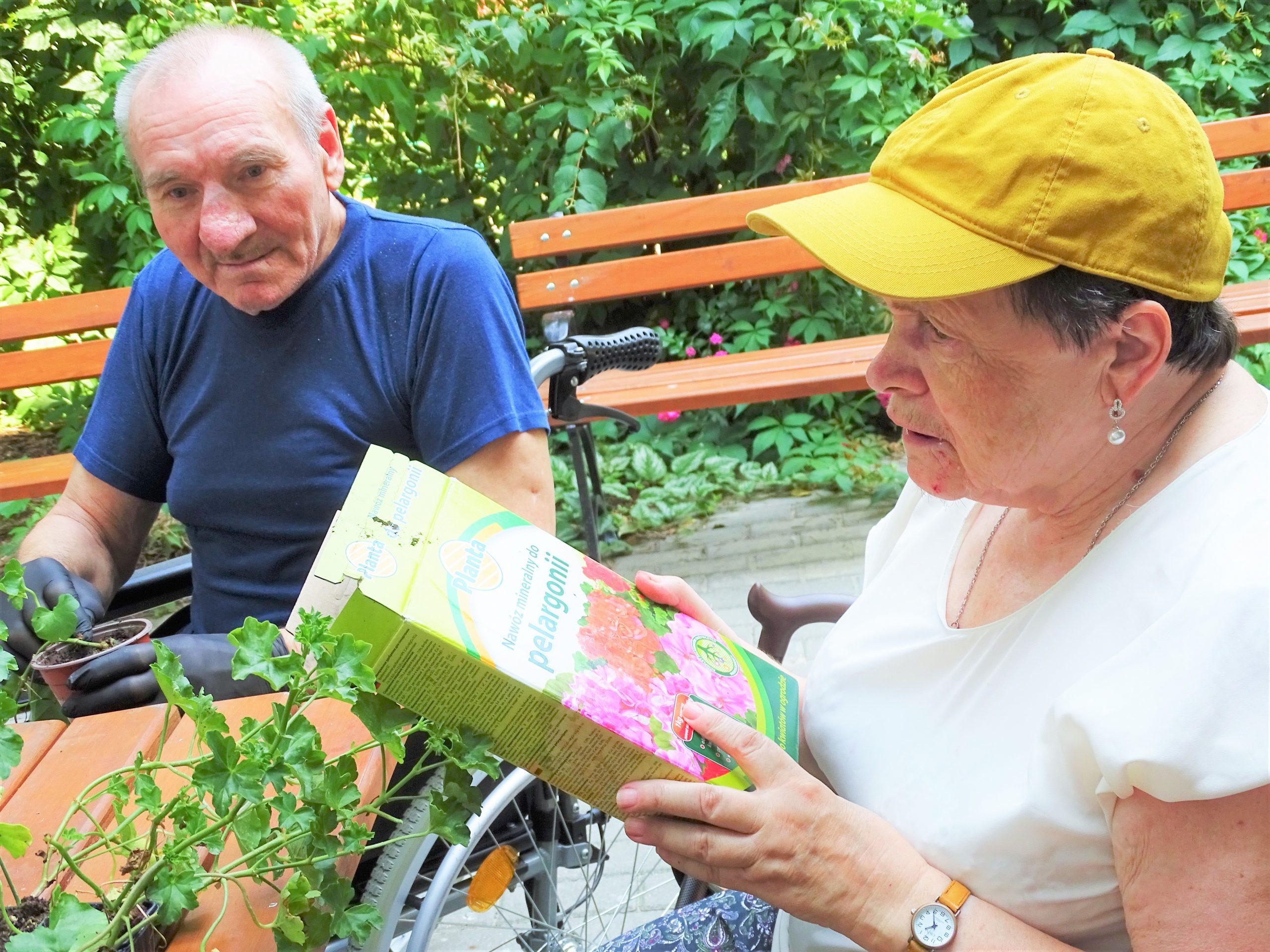 Kobieta i mężczyzna w ogrodzie sensorycznym pielęgnują kwiaty