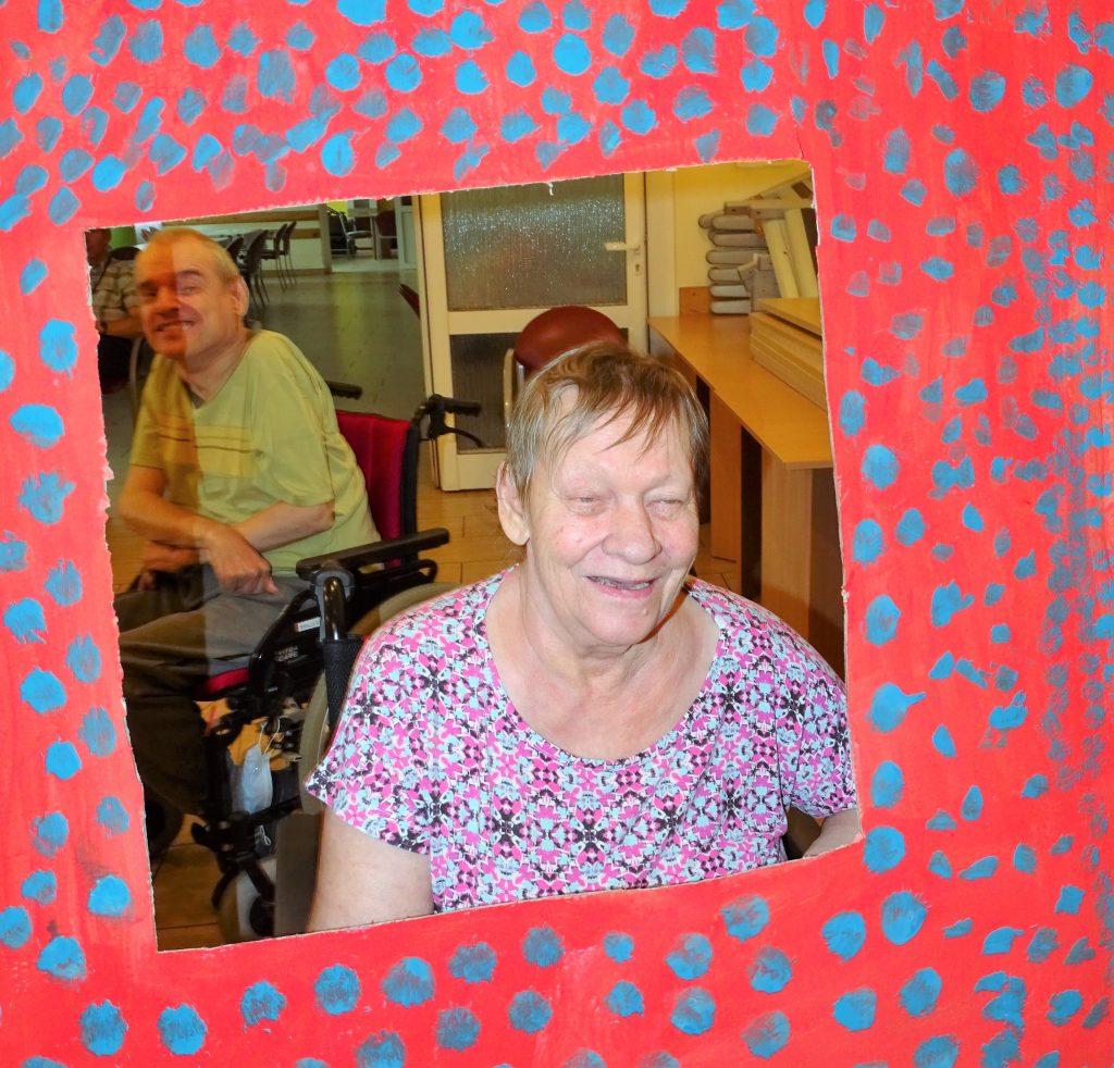 Uśmiechnięta kobieta pozuje w fotoramce, w tle uśmiechnięty mężczyzna na wózku