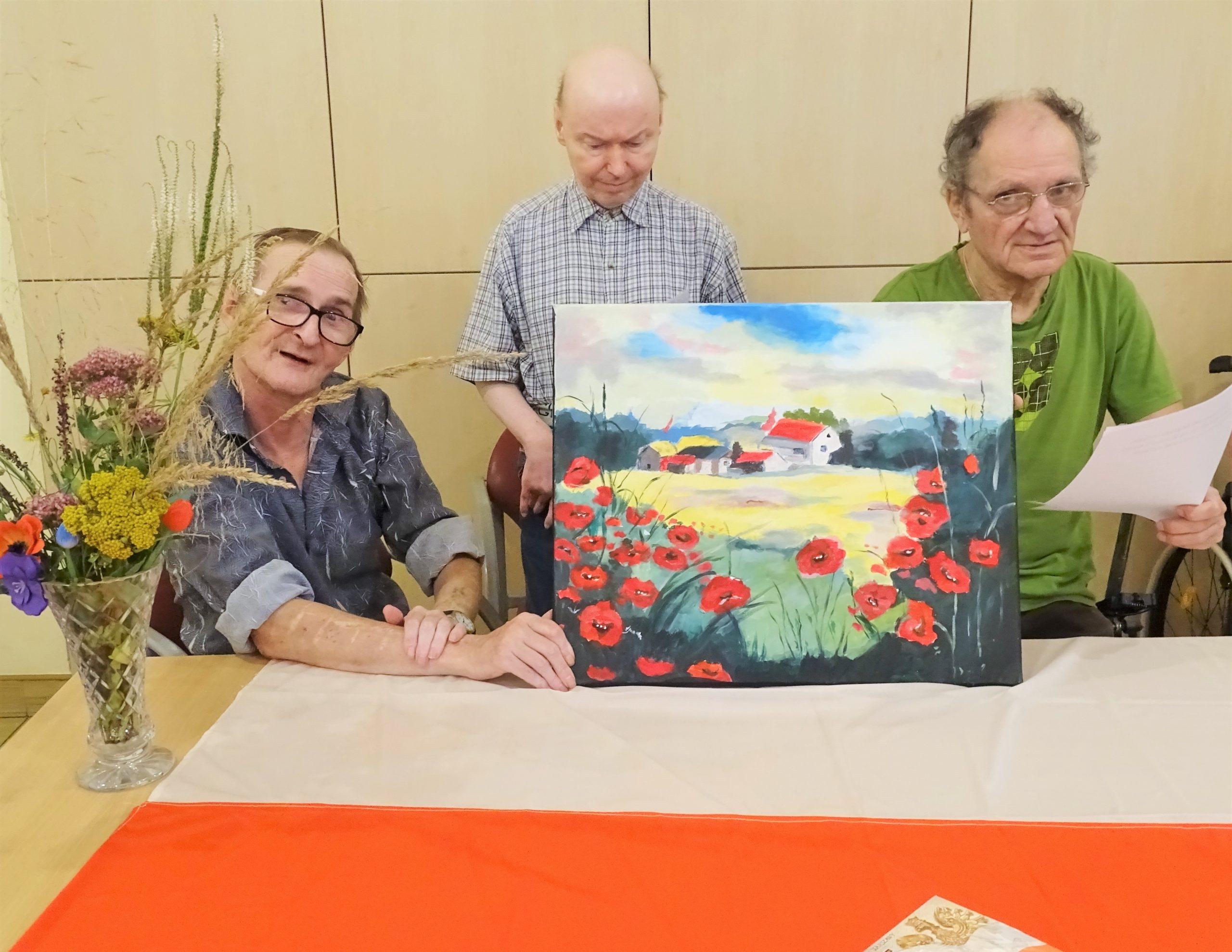 Trzech mężczyzn pozujących z obrazem, w tle dzbanek z bukietem kwiatów i biało czerwona flaga polski