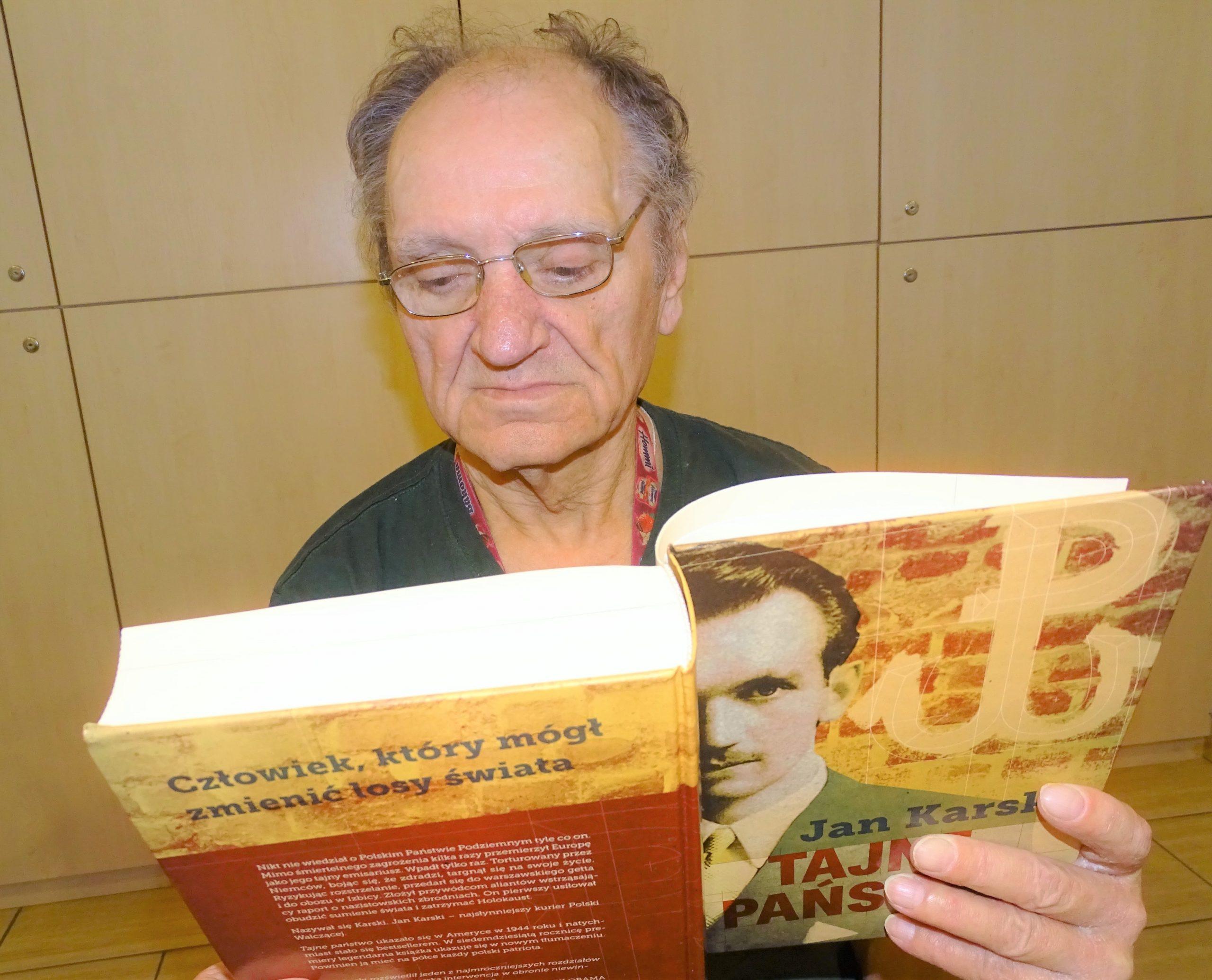 """Starszy mężczyzna czyta książkę Jana Karskiego """"Tajne Państwo"""""""