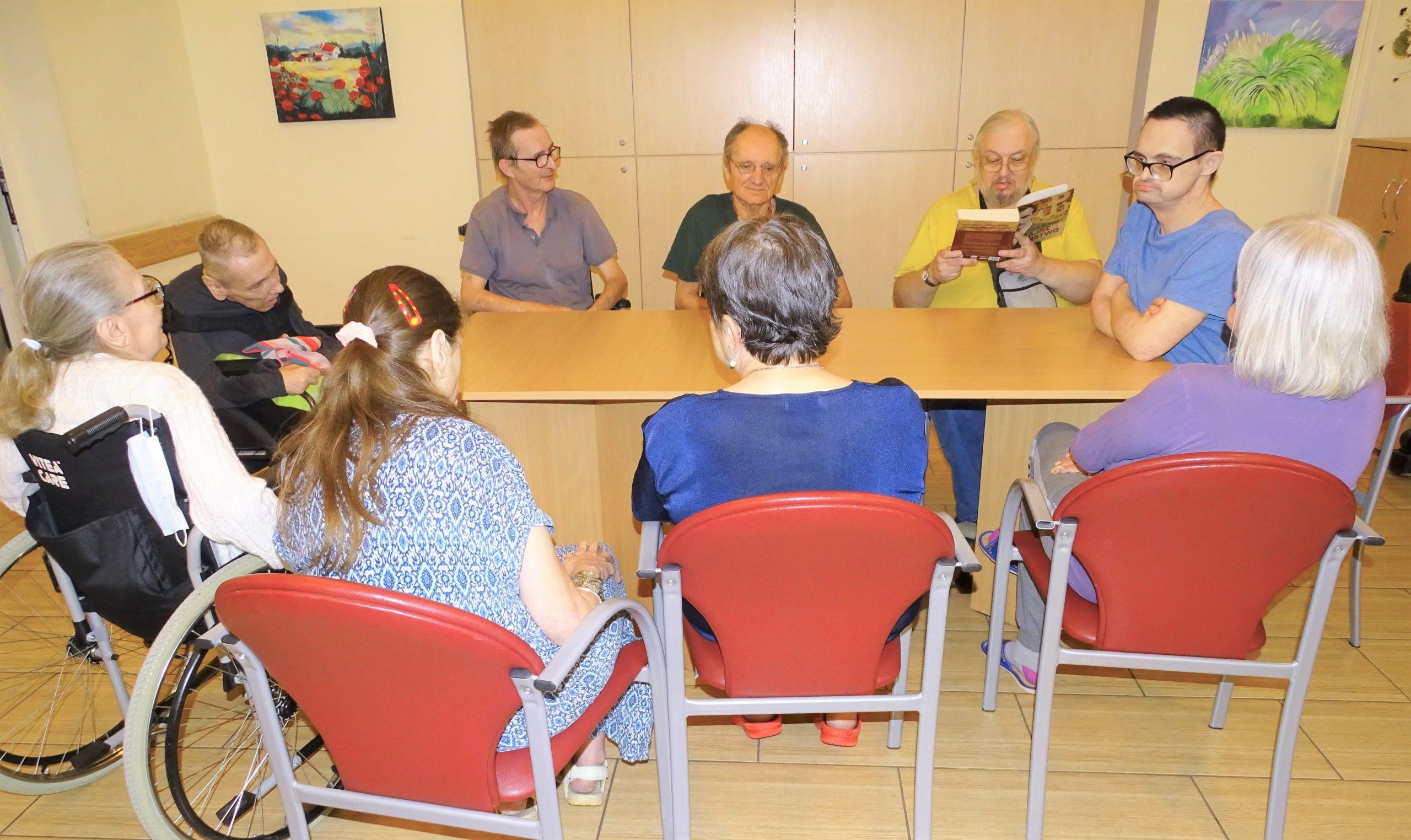 Mężczyzna w żółtej koszuli czyta książkę, pozostali seniorzy słuchają.