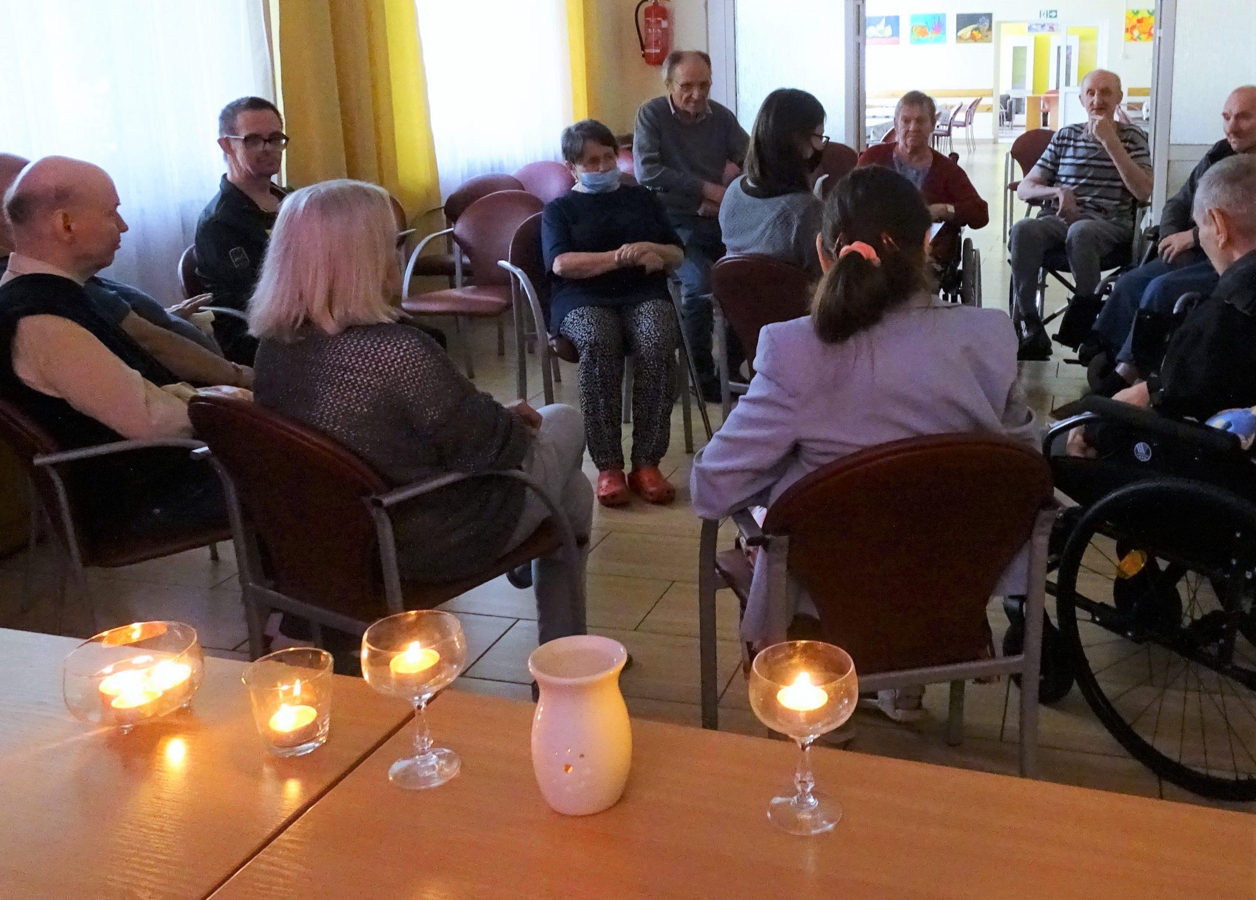 na pierwszym planie zdjęcia świeczniki, w tle seniorzy biorący udział w warsztatach relaksacyjnych