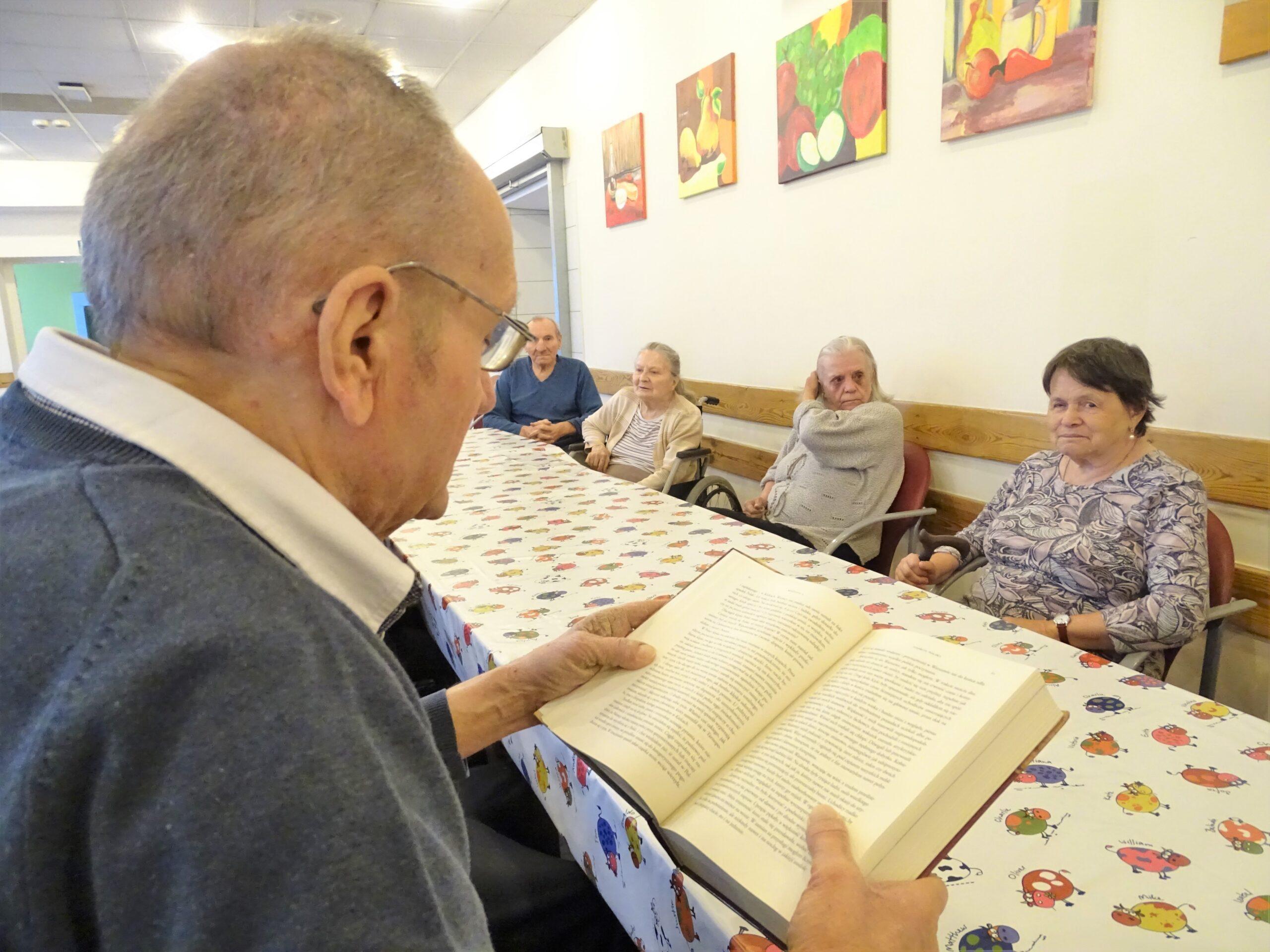 Mężczyzna czyta książkę, w tle seniorzy siedzący i słuchający mężczyzny
