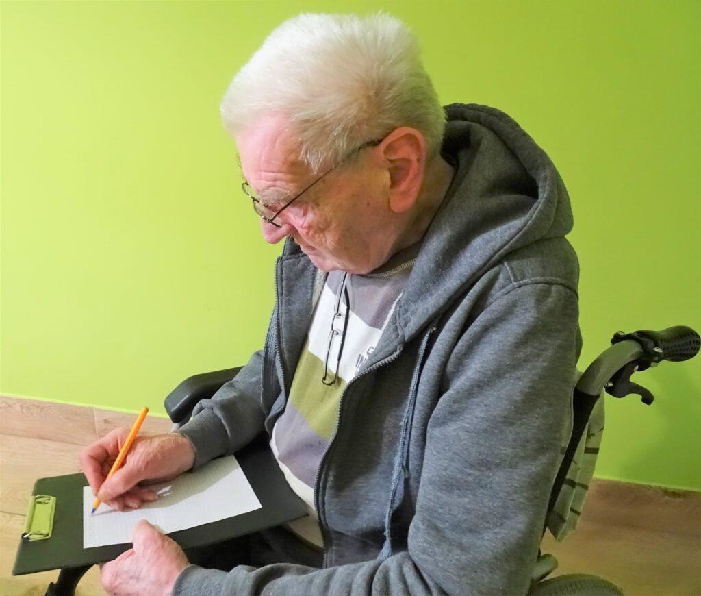 Starszy mężczyzna piszący na kartce list
