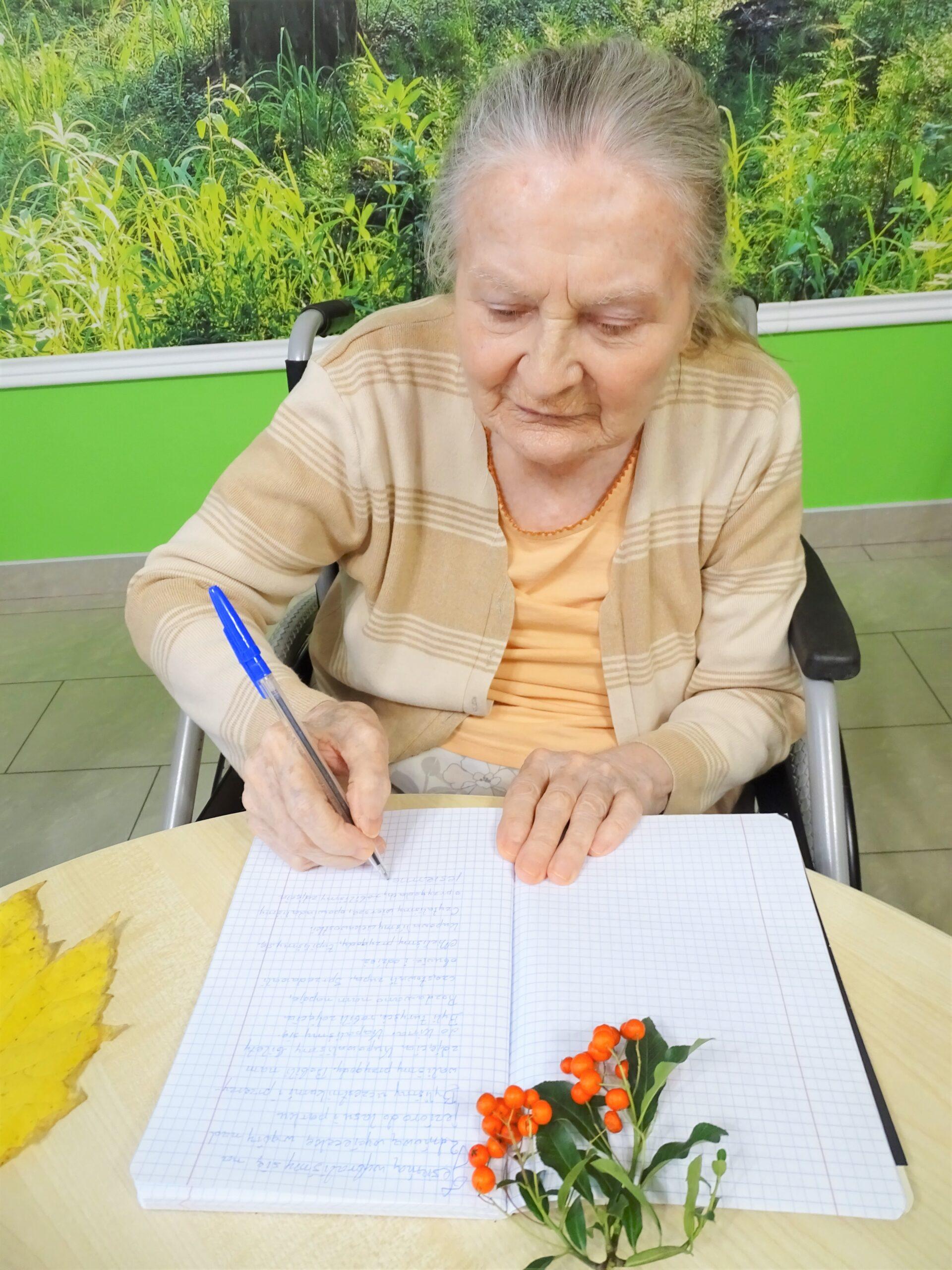 Starsza kobieta siedzi przy stole udekorowanym jesiennymi rekwizytami, notuje coś w zeszycie