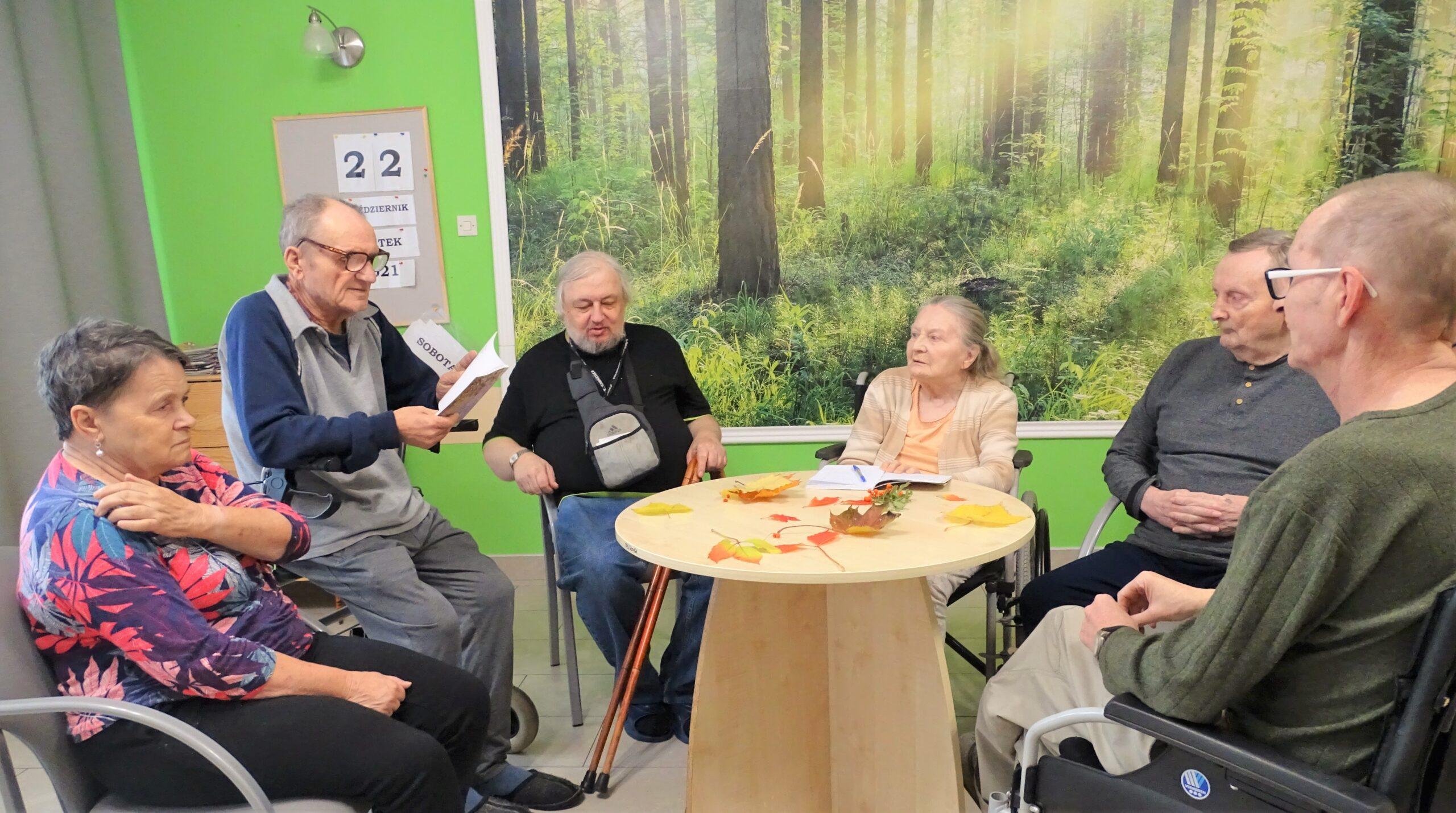 Grupa Mieszkańców siedzi przy stole ozdobionym jesiennymi liśćmi